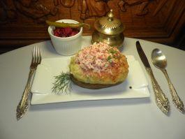 Ant grotelių keptos didelės bulvės su sūriu, krabų lazdelėmis ir aštriomis raugintų kopūstų salotomis