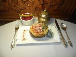 Ant grotelių keptos didelės bulvės su sūriu, kumpiu ir aštriomis raugintų kopūstų salotomis
